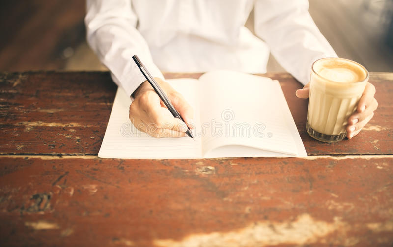 Bemannen Sie Schreiben im Notizblock mit Tasse Kaffee in der linken Hand auf hölzernem stockfoto