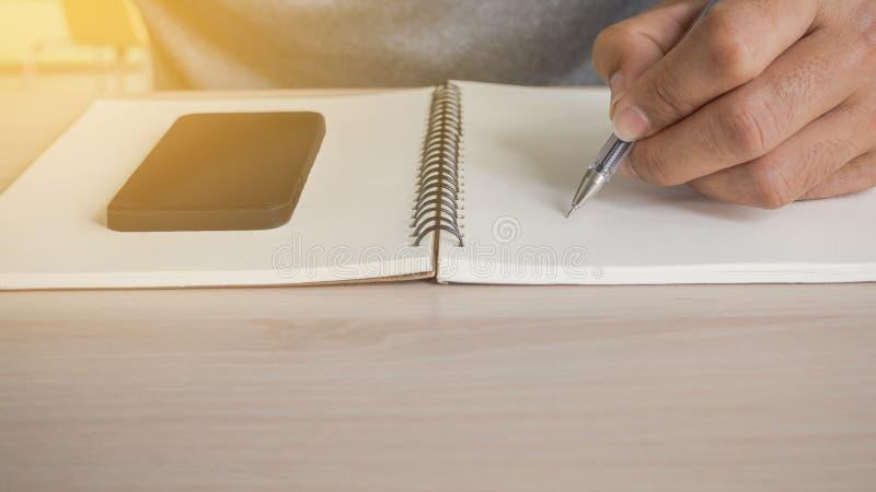 Bemannen Sie Schreiben am Notizbuch und am Telefon auf Notizbuch stockfotografie