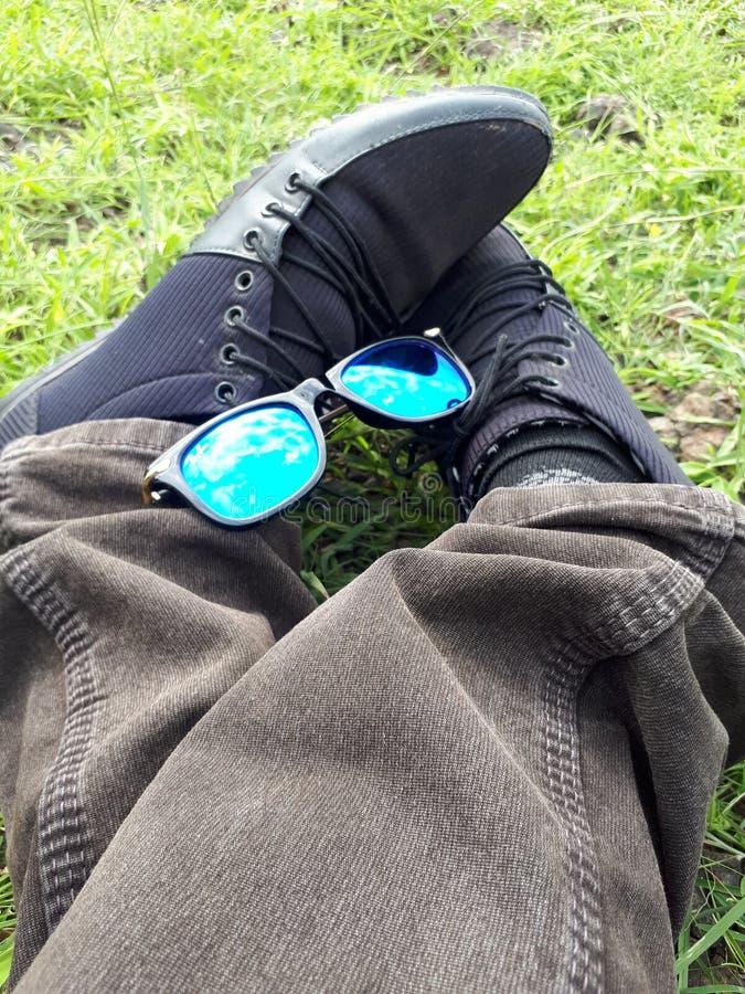 Bemannen Sie Schuhe mit Sonnenbrille im Park, Sonnenbrille, Segeltuch-Schuhe, der Mann, der im Park stationiert lizenzfreie stockbilder