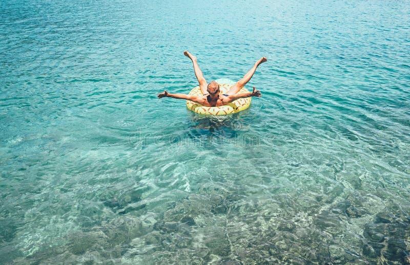 Bemannen Sie Schwimmen auf aufblasbarem Ananaspoolring im haarscharfen Meer lizenzfreie stockfotos