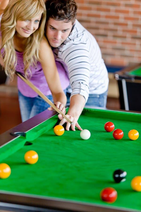 Bemannen Sie, seine Freundin beibringend, wie man Pool spielt lizenzfreies stockbild