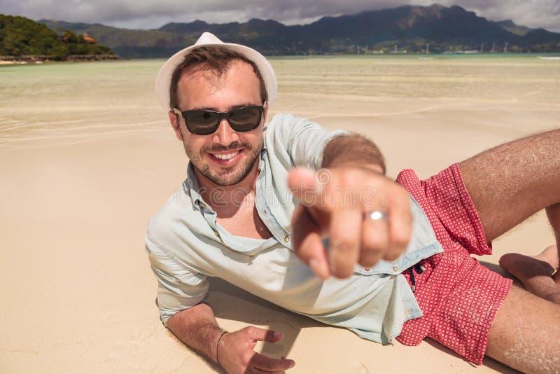 Bemannen Sie sich hinlegen auf dem Strand und zeigt Finger stockfoto