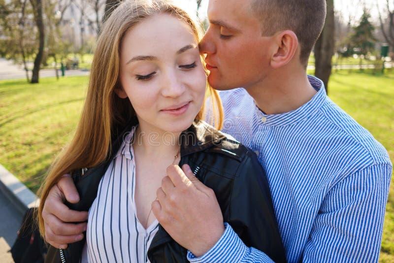 Bemannen Sie sich kümmern um seiner Freundin, die sie mit Jacke und hugg beschichtet stockfotografie