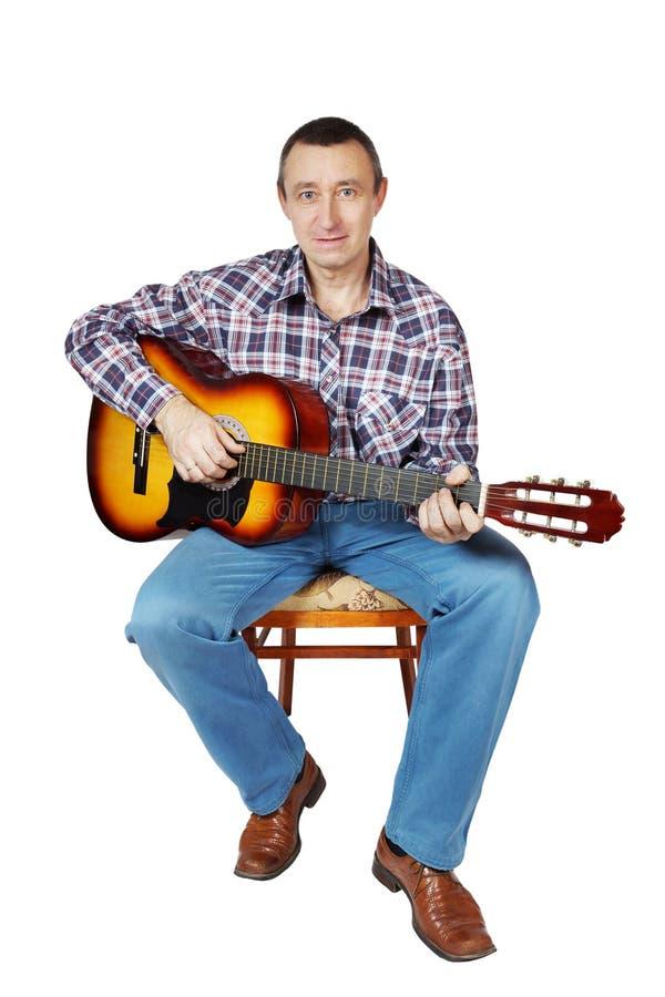 Bemannen Sie Spiele eine Gitarre, die auf einem Stuhl sitzt stockfotografie