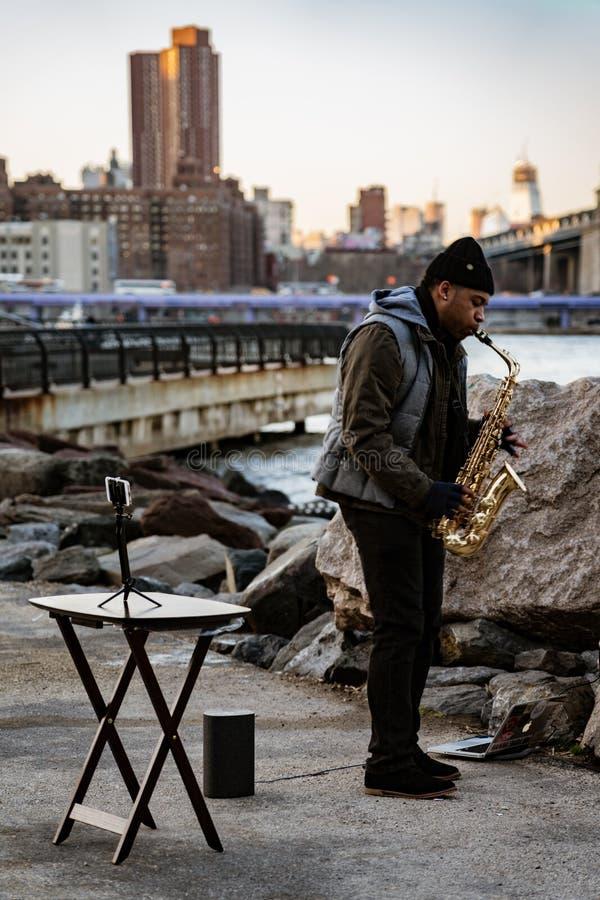 Bemannen Sie Spielsaxophon für Spenden in Dumbo-Park lizenzfreies stockfoto