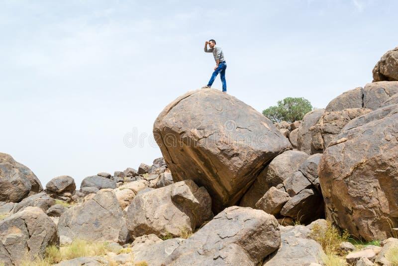Bemannen Sie Stellung auf einem Felsen und weit weg schauen stockbild