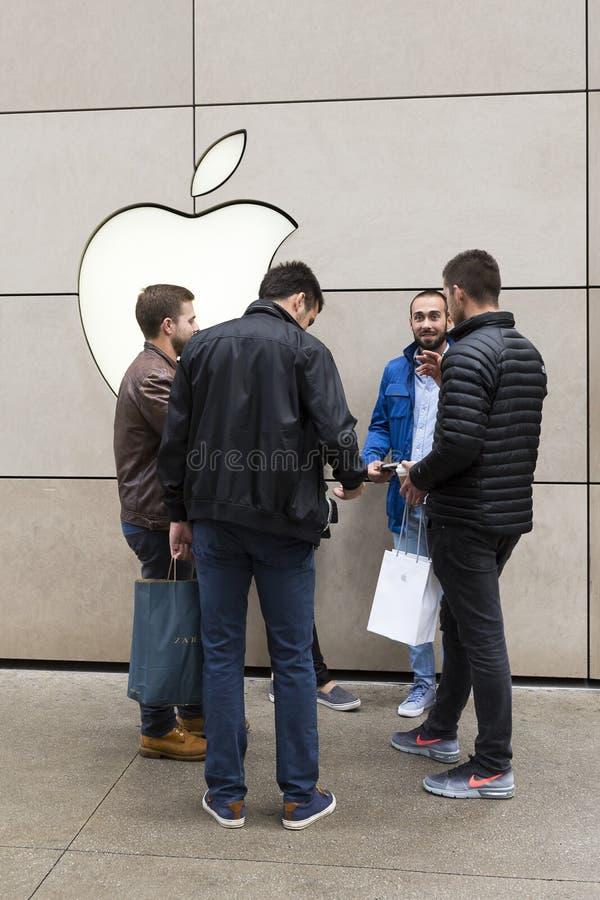 Bemannen Sie Stellung mit drei männlichen Freunden, die außerhalb Michigan-Allee Apple Store rauchen stockfoto