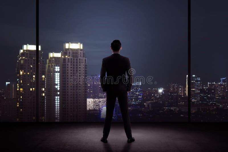 Bemannen Sie Stellung in seinem Büro, welches die Stadt nachts betrachtet lizenzfreie stockbilder