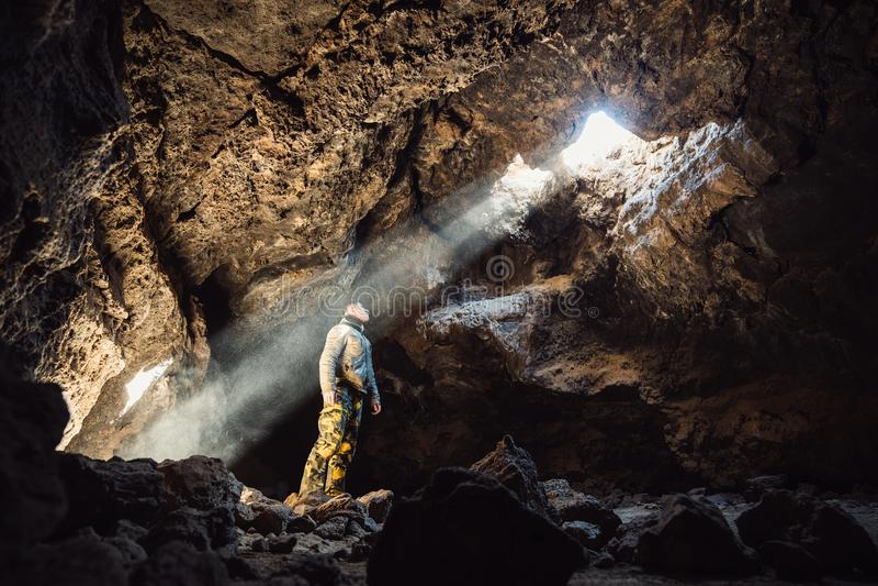 Bemannen Sie Stellung unter dem Licht in der Gebirgshöhle Extremes Abenteuerreisen concep lizenzfreie stockfotografie