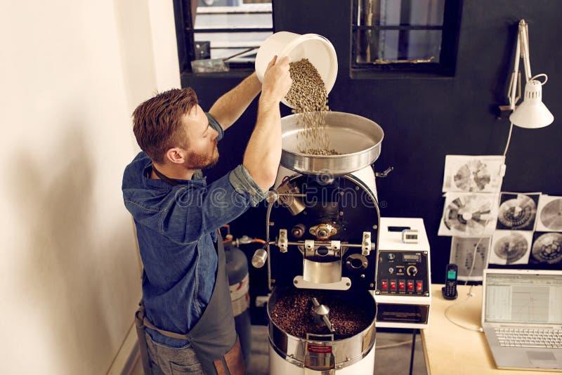 Bemannen Sie strömende Rohkaffeebohnen in eine moderne Maschine stockfotografie