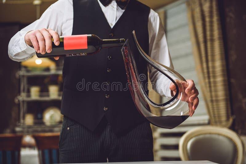 Bemannen Sie strömenden Rotwein in würdevolles Dekantiergefäß stockfotos