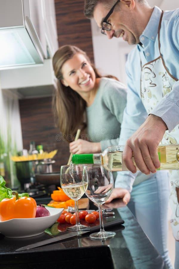 Bemannen Sie strömendes Weißwein in den Gläsern beim Kochen mit Frau an der Küche lizenzfreie stockbilder