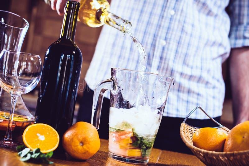 Bemannen Sie strömendes Weißwein in ein Glas stockbild