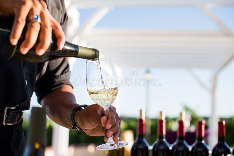 Bemannen Sie strömendes Weißwein in ein Glas lizenzfreie stockbilder