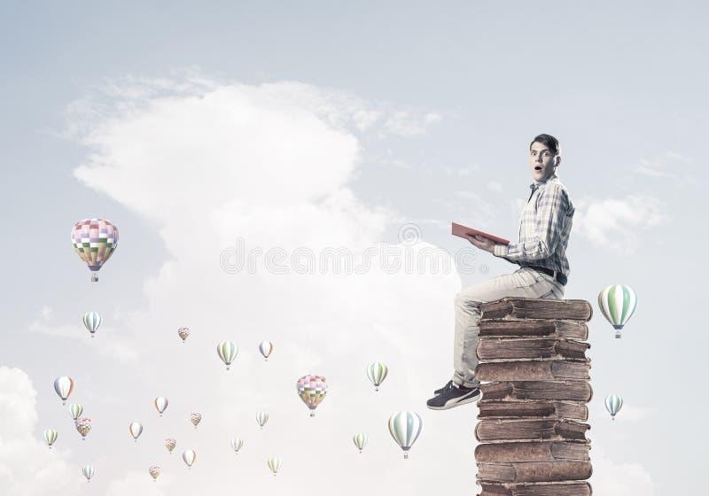Bemannen Sie Studenten auf Stapellesebuch und die Luftfahrzeuge, die herum fliegen stockfotografie