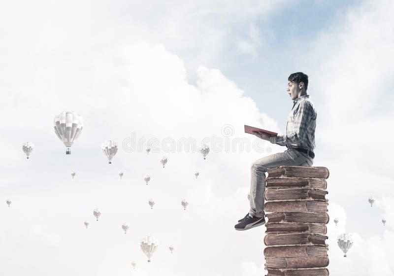Bemannen Sie Studenten auf Stapellesebuch und die Luftfahrzeuge, die herum fliegen lizenzfreie stockfotos