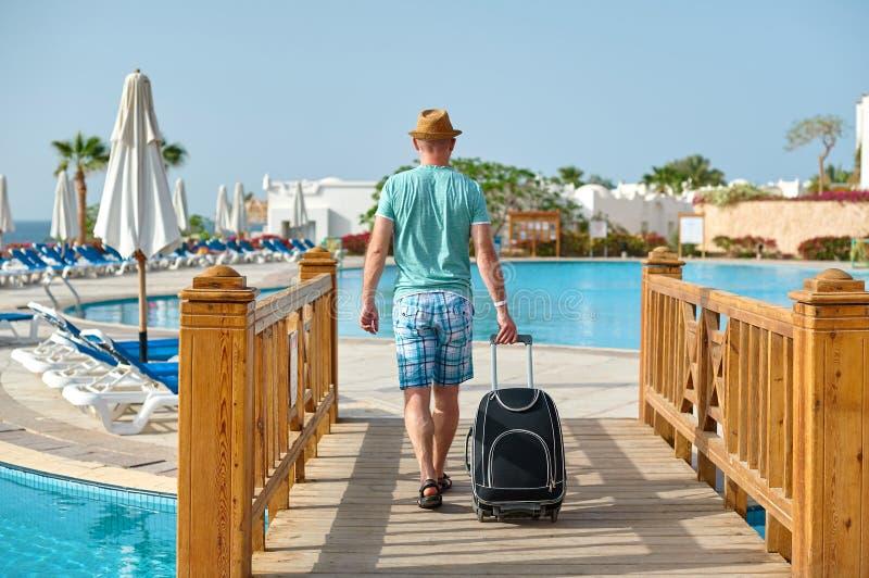Bemannen Sie Touristen in der Sommerkleidung mit einem Koffer in seiner Hand und das Meer auf dem Strand betrachten, Pool im Hote stockfotografie