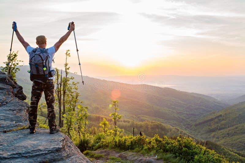 Bemannen Sie Touristen mit Wanderstöcken auf Hügel bei Sonnenaufgang stockfotografie