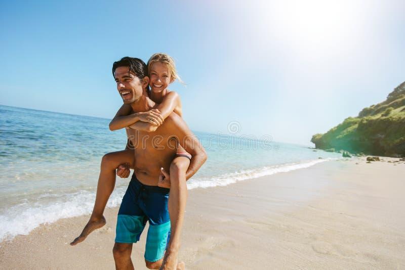 Bemannen Sie tragende Freundin auf seinem zurück entlang dem Seeufer stockfotos