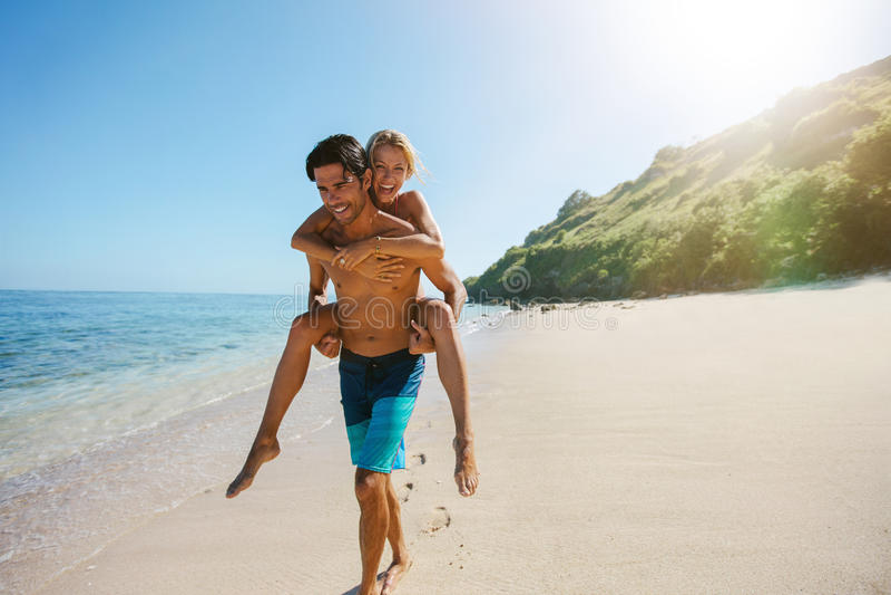 Bemannen Sie tragende Freundin auf seinem zurück entlang dem Strand lizenzfreie stockfotografie