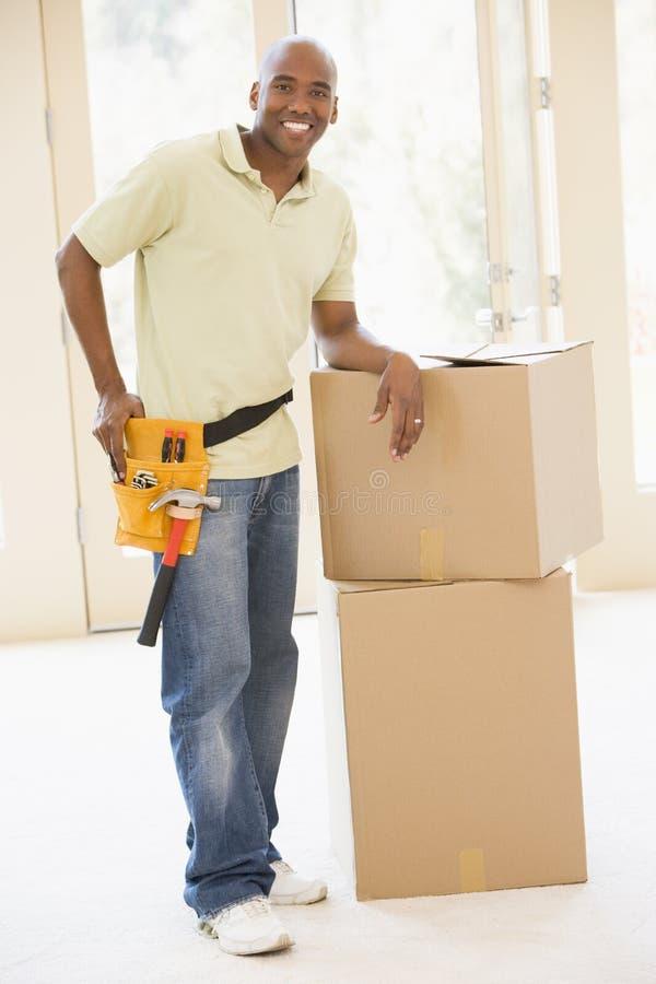 Bemannen Sie tragenden Hilfsmittelgurt durch Kästen im neuen Haus lizenzfreies stockbild