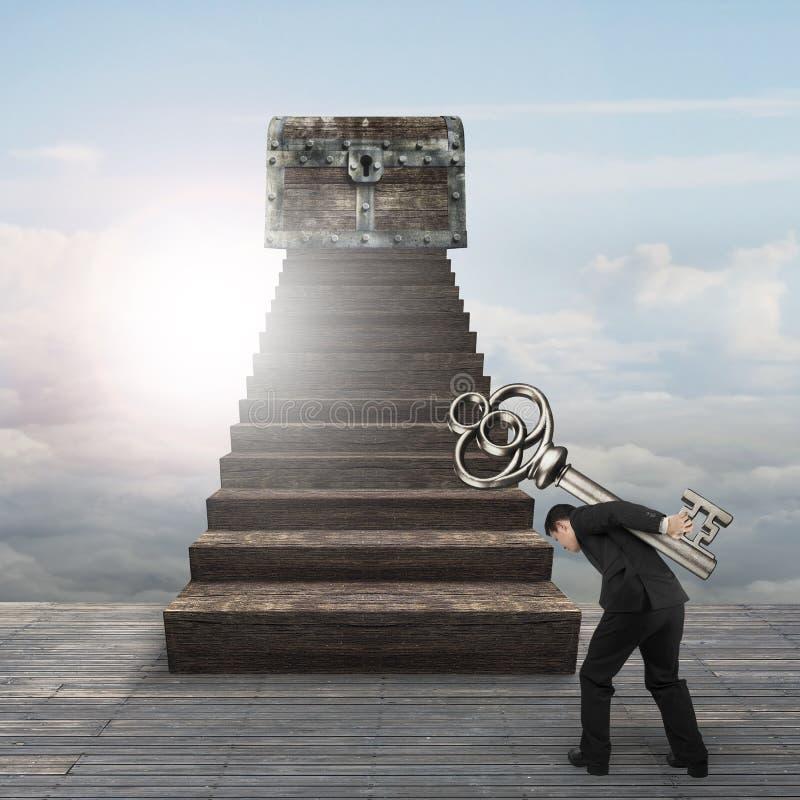Bemannen Sie tragenden Schlüssel in Richtung zur Schatztruhe auf hölzerner Treppe stockbild