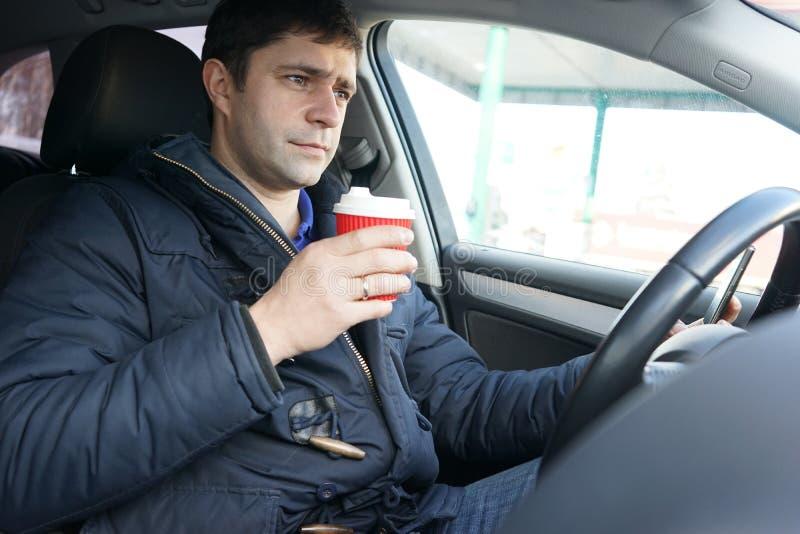 Bemannen Sie trinkenden Kaffee im Auto an der Tankstelle stockbild