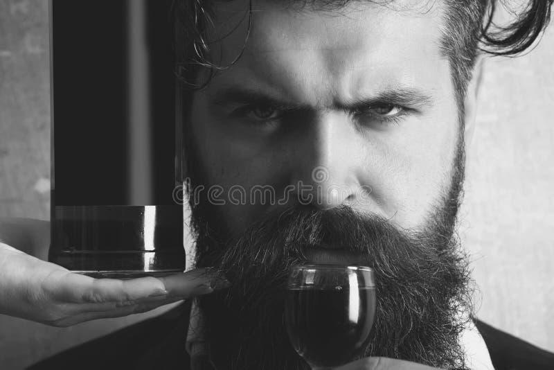 Bemannen Sie trinkenden Wein vom Glas mit Flasche auf weiblicher Hand stockbild