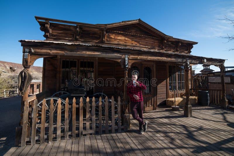 Bemannen Sie Trinkwasser vor altem Holzhaus im Cowboygrafschaftsdorf stockfoto