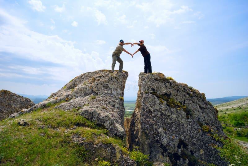 Bemannen Sie und die Frau faltete ihre Hände in einer Herzform und stand auf Berg hoch lizenzfreie stockfotografie