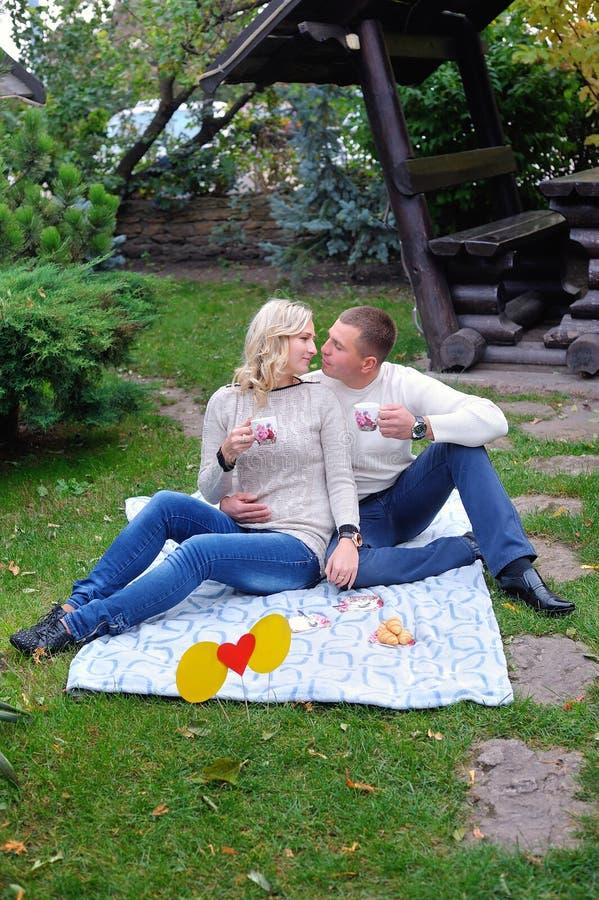 Bemannen Sie und eine Frau, die auf einem Bett im Park sitzt, der ein Picknick hat stockbilder