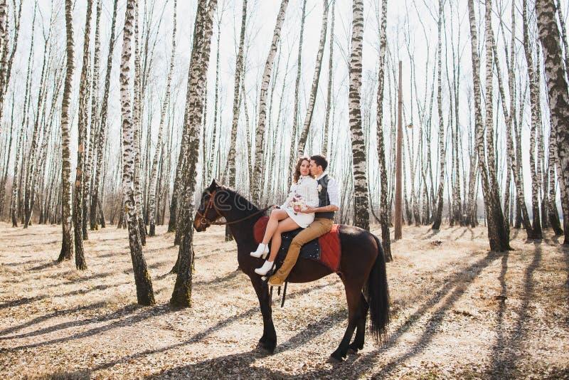 Bemannen Sie und eine Frau, die zusammen braunes Pferd reitet stockfotografie