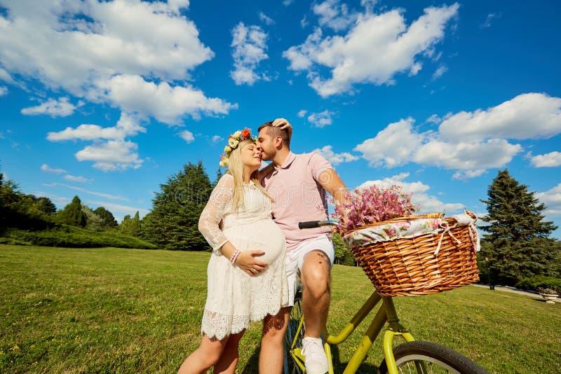 Bemannen Sie und eine Frohnatur der schwangeren Frau im Park Junges glückliches famil stockfoto