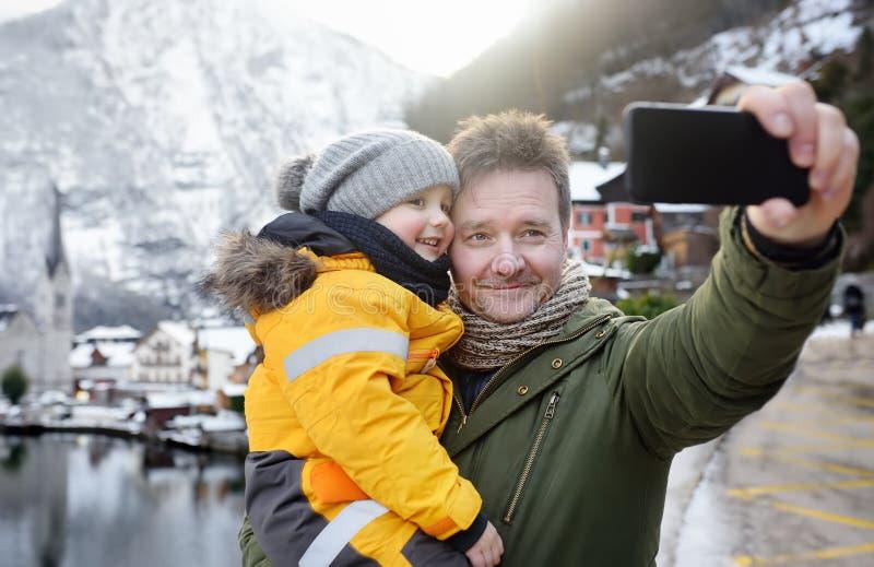 Bemannen Sie und sein kleiner Sohn, der selfie bewegliches Foto mit szenischer Ansicht des Winters des Dorfs von Hallstatt auf Hi stockfoto