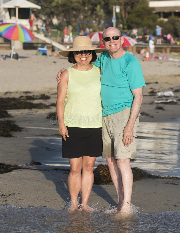 Bemannen Sie und seine Frau, die Spaß auf dem Strand hat lizenzfreie stockbilder
