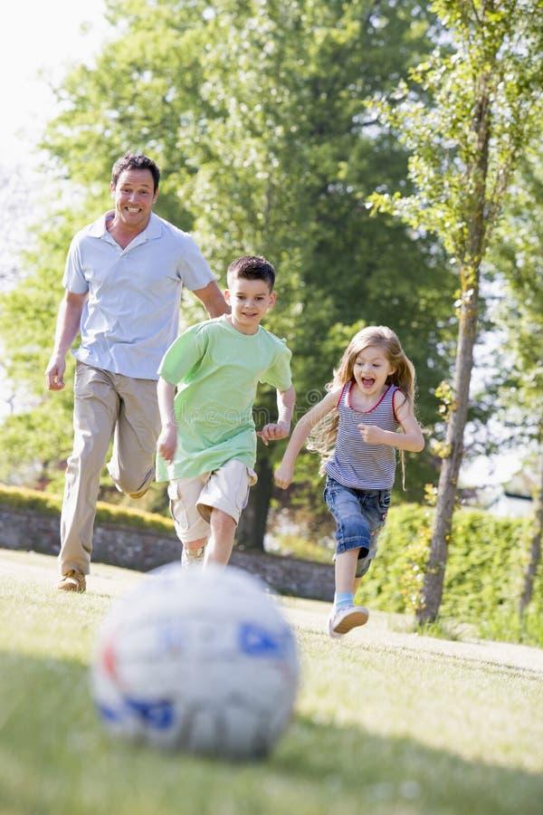 Bemannen Sie und zwei junge Kinder, die draußen Fußball spielen lizenzfreie stockbilder