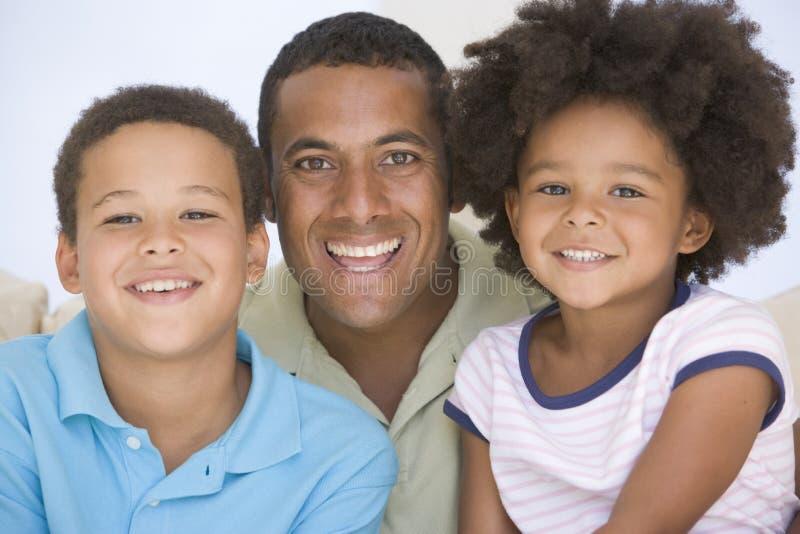 Bemannen Sie und zwei junge Kinder, die im Wohnzimmer sitzen lizenzfreies stockbild