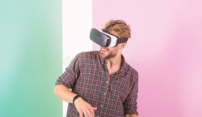 Bemannen Sie unrasierten Kerl mit VR-Gläsern, rosa Hintergrund Genießen Sie virtuelle Realität Moderne Technologien des Hippie-Ge stockfoto