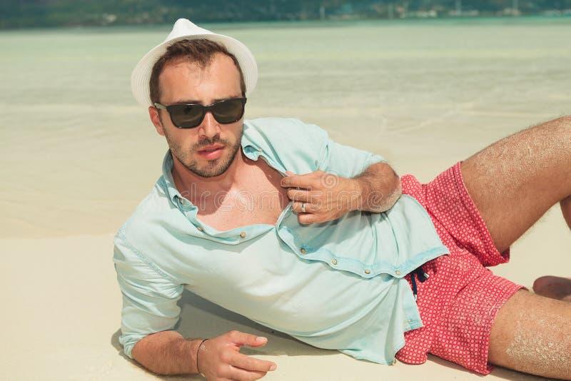 Bemannen Sie unten an liegen der Strand mit weißem Hut und Sonnenbrille stockbild