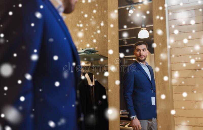 Bemannen Sie versuchende Jacke an am Spiegel im Bekleidungsgeschäft stockfotografie