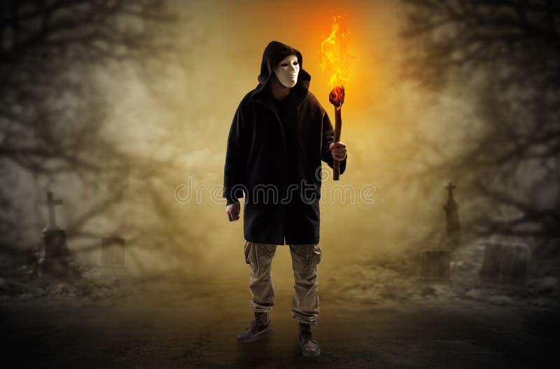 Bemannen Sie von einem Dickicht mit brennendem Flambeau herauskommen lizenzfreie stockbilder