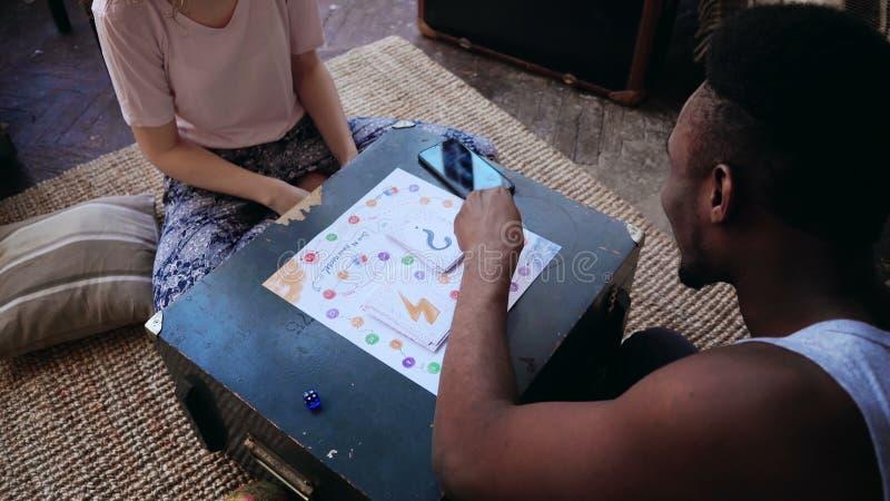 Bemannen Sie Würfe die Würfel, sitzt vor Frau Gemischtrassige Paare in den Pyjamas, die das Brettspiel auf dem Boden spielen lizenzfreie stockbilder