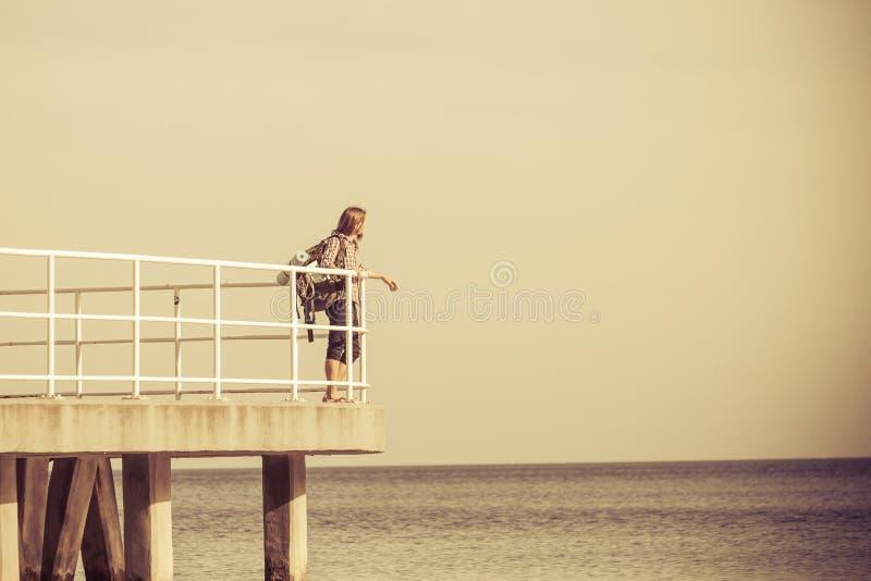 Bemannen Sie Wanderer mit Rucksack auf Pier, Seelandschaft lizenzfreie stockfotografie