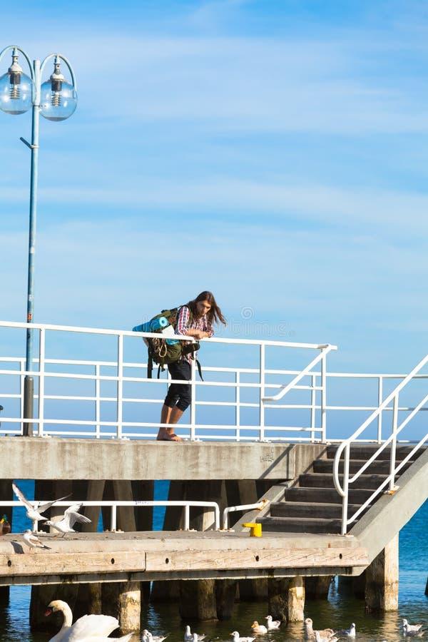 Bemannen Sie Wanderer mit Rucksack auf Pier, Seelandschaft stockfoto