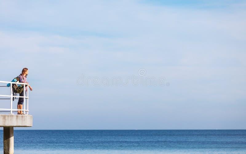 Bemannen Sie Wanderer mit Rucksack auf Pier, Seelandschaft lizenzfreies stockbild