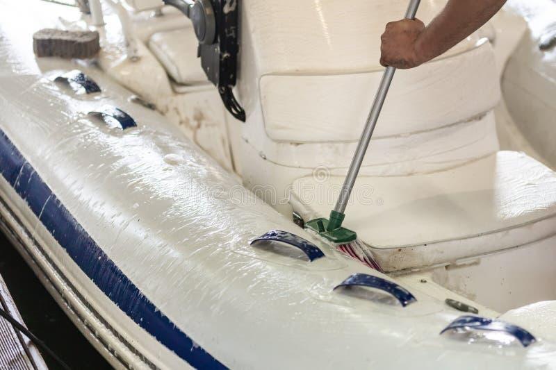Bemannen Sie waschendes weißes aufblasbares Boot mit Bürste und Druckwassersystem an der Garage Schiffsservice und Saisonwartungs lizenzfreie stockbilder