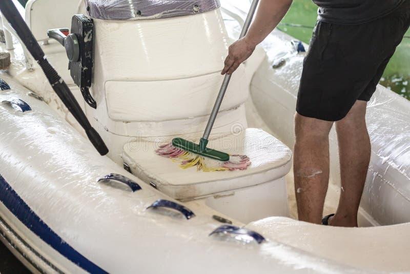 Bemannen Sie waschendes weißes aufblasbares Boot mit Bürste und Druckwassersystem an der Garage Schiffsservice und Saisonwartungs lizenzfreies stockbild