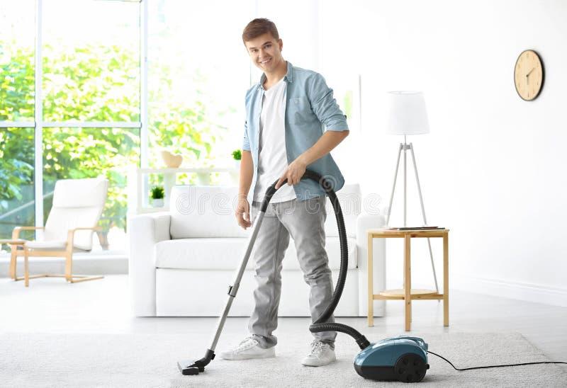 Bemannen Sie weißen Reinigungsteppich mit Vakuum im Wohnzimmer stockbilder