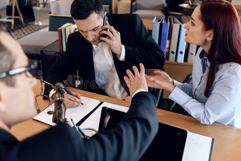 Bemannen Sie, wem seine Frau sich berät am Telefon mit Rechtsanwalt scheidet Distempered-Frau sitzt nahe bei dem Mann, der am Tel stockbild