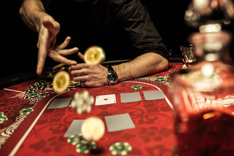 Bemannen Sie werfende Pokerchips auf Tabelle beim Spielen des Pokers stockfoto